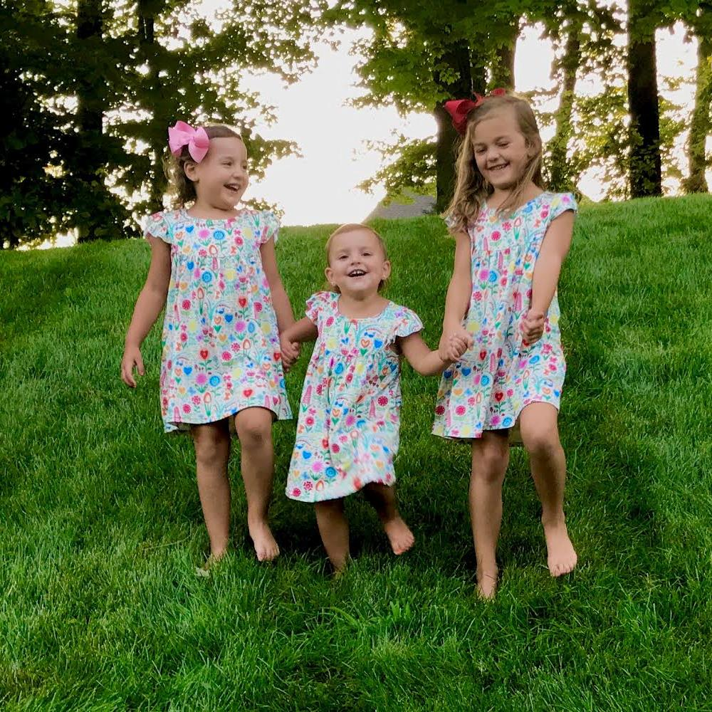Three little girls playing and laughing on the lawn wearing our dutch garden print flutter sleeve lap dress