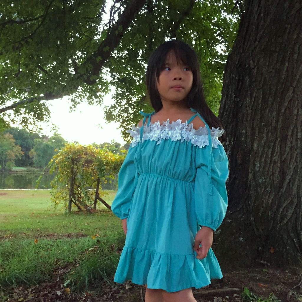 Little girl in our off shoulder peasant dress in teal