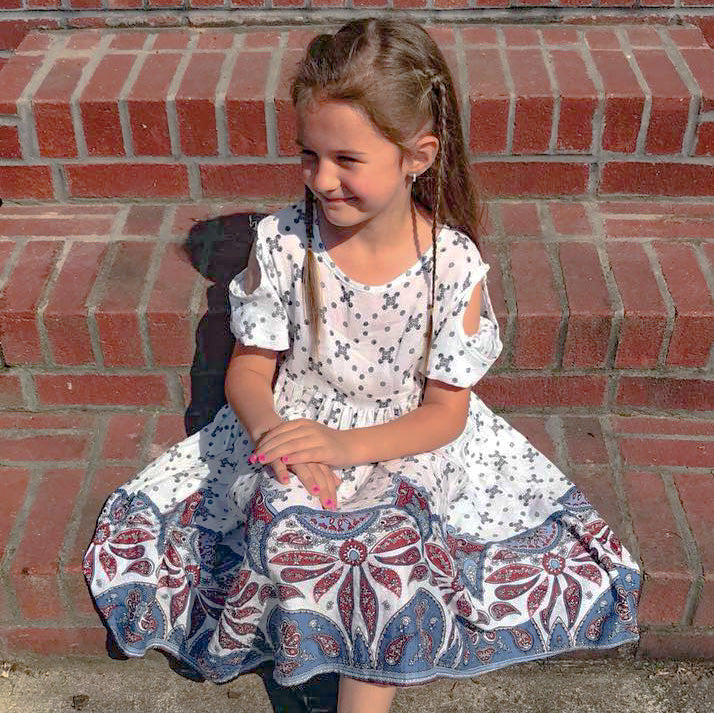 Little girl wearing our linen cold shoulder dress