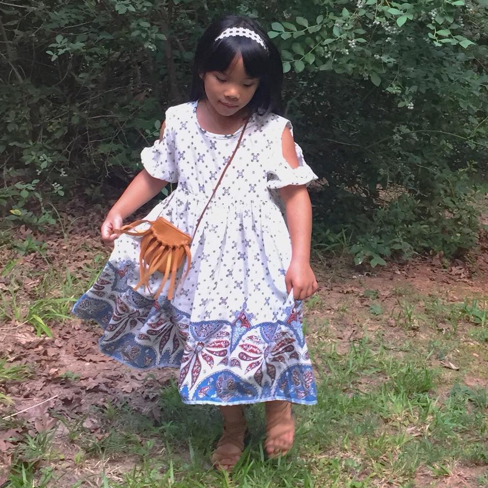 Little girl wearing out paisley boho cold shoulder dress and leather fringe crossbody bag in brown