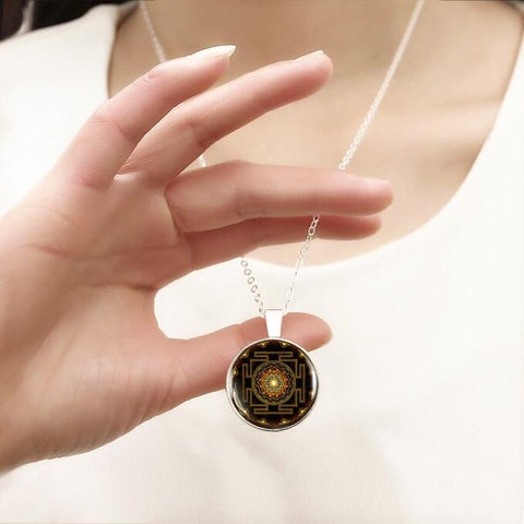 Picture of sri yantra buddhist necklace being worn by a person.