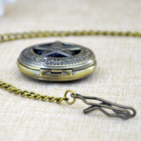 View of pentagram pocket watch lying on a table.