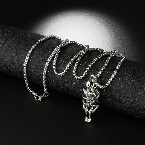 Picture of two skeletons hugging necklace against black background.