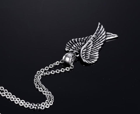Folded angel wings necklace against a black background.