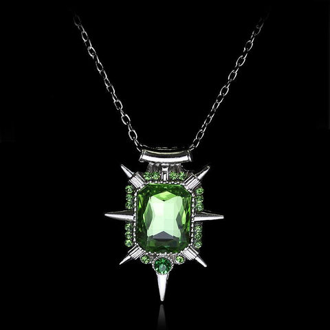 Green witch necklace on a black background.