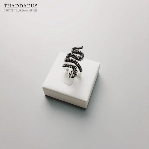 Black pave zirconia snake ring on box.