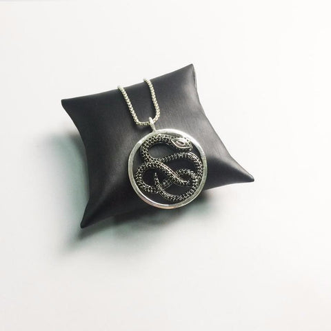 Black pave zirconia snake necklace on a pillow.