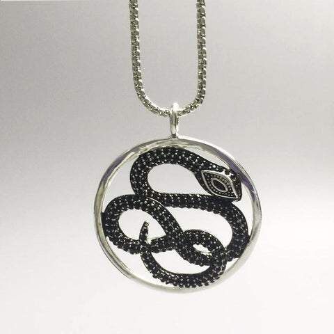 Black pave zirconia snake necklace hanging by its chain.