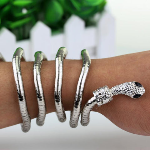 Picture of the serpent bracelet in silver around someone's arm.