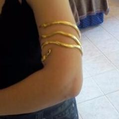 Picture of the serpent bracelet in gold around someone's upper arm.
