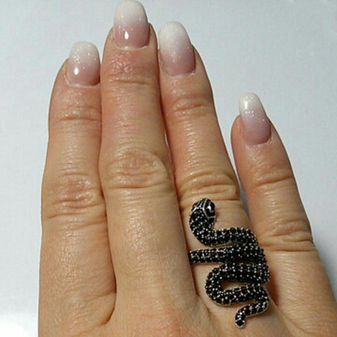 Black pave zirconia snake ring on a person's finger.