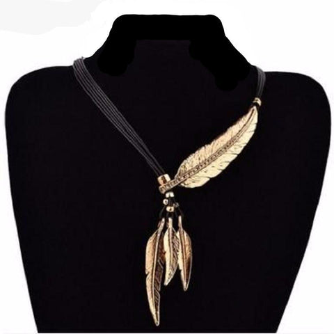 Feather necklace in gold on black display.