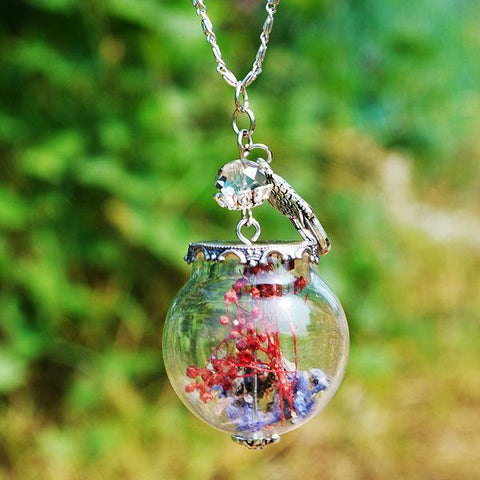 Close up of globe necklace with herbs inside against a garden setting.