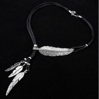 Feather necklace in silver against a black background.