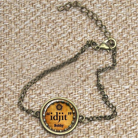 """idjit"" pendant bracelet in bronze against a fabric background."