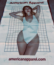An American Apparel billboard with a girl in a white swimsuit standing against a wire grid background.