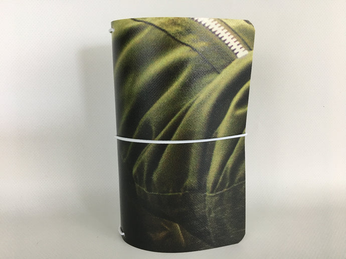 Field Note size refillable notebook cover with an olive green image from recycled vinyl billboard.