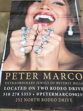 A vinyl billboard for Peter Marco in Beverly Hills featuring a woman with diamond rings on every finger.