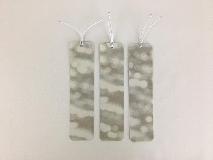 3 bookmarks with an abstract tan and white pattern made from billboard vinyl.