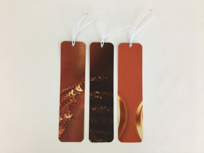 3 bookmarks with a burnt orange and gold pattern made from billboard vinyl.