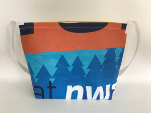 Billboard vinyl tote bag with blue and orange patterns.