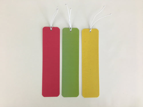 3 bookmarks, neon pink, green, and yellow, made from billboard vinyl.