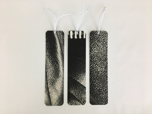 3 bookmarks with a black and white pattern made from billboard vinyl.
