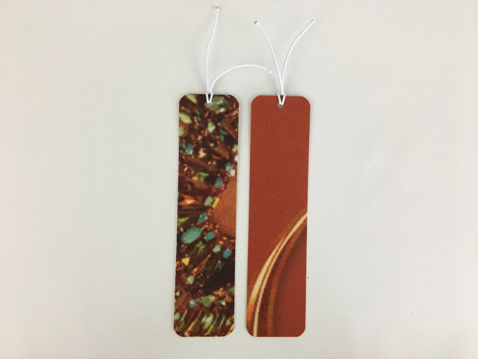 2 bookmarks, burnt orange with a jewelry pattern, made from billboard vinyl.