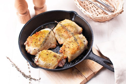 Browned chicken thighs prepared and photographed in a skillet.