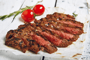 Rare flank steak prepared and served on a parchment paper with a garnish of tomato
