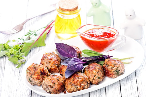 Lightly browned turkey meatballs prepared with spices, on a white plate and kitchen utensils