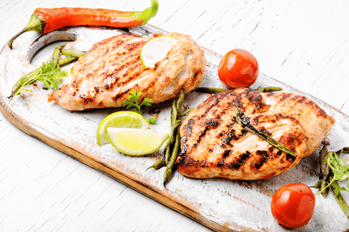 Grilled chicken prepared on a wood cutting board, garnished with tomato and pepper