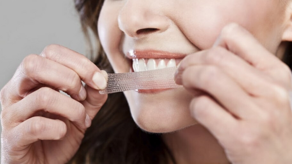 a lady showing teeth whitening strips