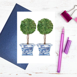 A blue and white card with topiary trees
