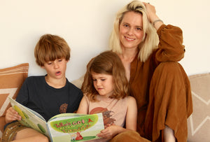Author and Owner of Salty Avalon Belinda Nowell reads her book Who's Got a Normal Family? to children. Belinda wears a rust coloured jumpsuit by fashion designer Rabens Saloner.
