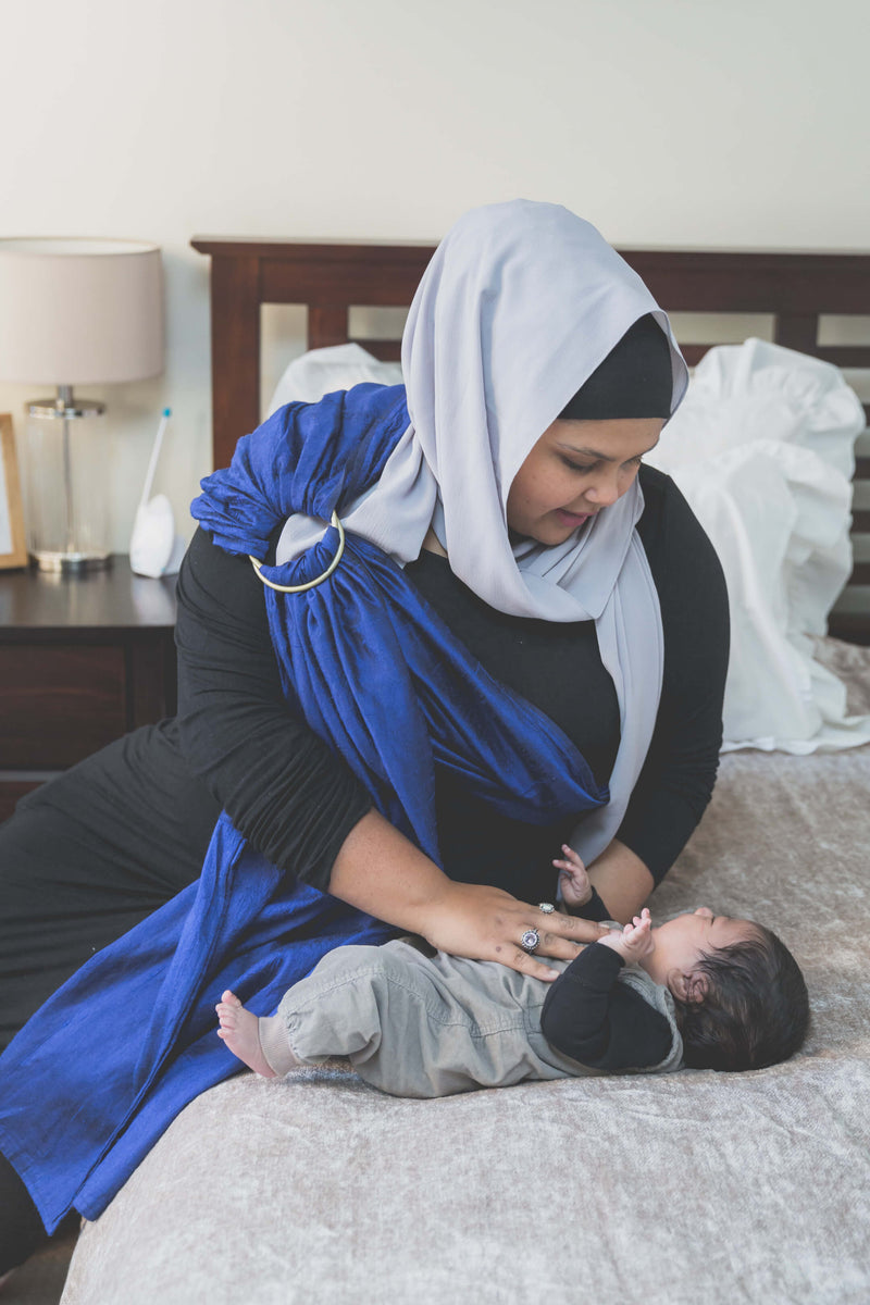 Muslim woman in hijab holding her newborn son wearing a Zarinah ring sling