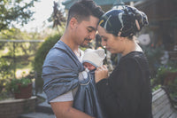 Image of a husband wife embracing while babywearing his newborn in a Zarinah ring sling