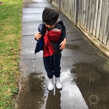 3 year old boy wearing his toy own in his red toy ring sling standing in front of a puddle. www.zarinah.com.au