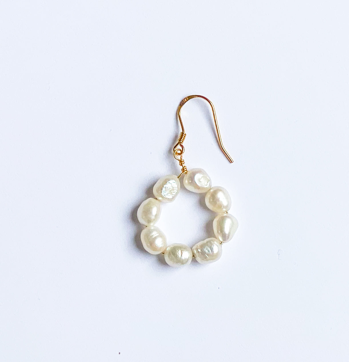 Filigree dangle earrings with freshwater pearls, arranged in a ring.