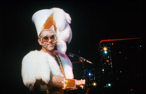 Elton John on stage in vintage sunglasses