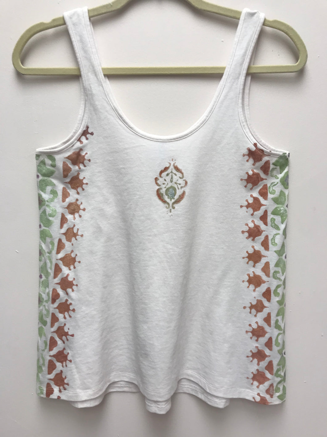 Relaxed fitting tank top with scoop neck and a back pleat in ecru, with a handprinted morroccan design printed on both sides of shirt with a center motif in front.