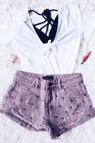 mauve studded denim high waisted shorts with a white bodysuit and black bralette