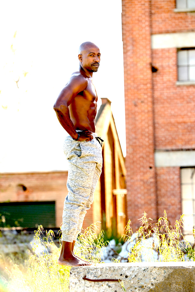 online mindset coach image of damon j smith standing on a stone with old brick building background. Side angle of chiseled abs and chest