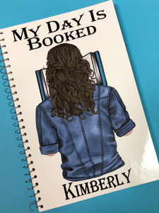 My Day is Booked personalized notebook featuring YOU on the front cover. Custom person has your hair color and style wearing your favorite shirt while reading a book.