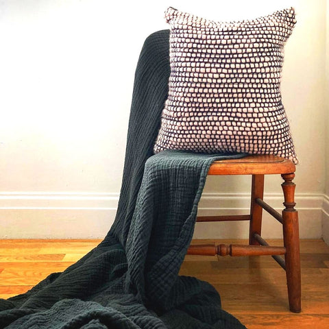 Pink and dark blue crocheted cushion sits on a wooden chair, which is draped in a dark grey cotton throw