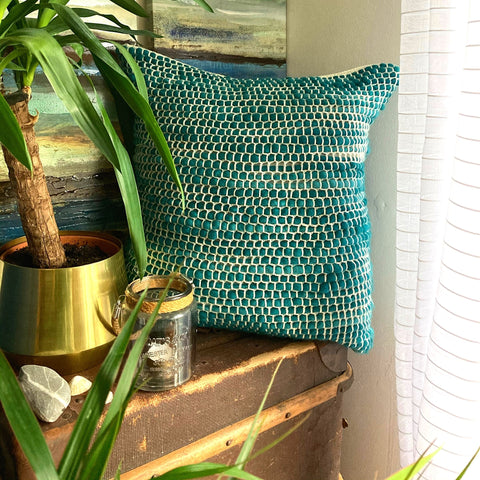 Teal and cream crocheted cushion on a brown trunk beside a window. Next to the cushion i a plant in a gold pot