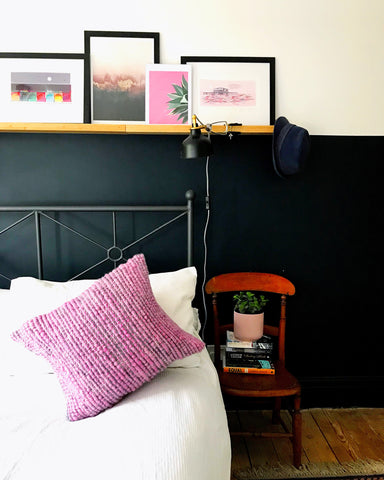 Pink and grey crocheted cushion on a white bed with a wooden chair beside the bed. There is a blue wall behind the bed, with a picture shelf with framed prints above.