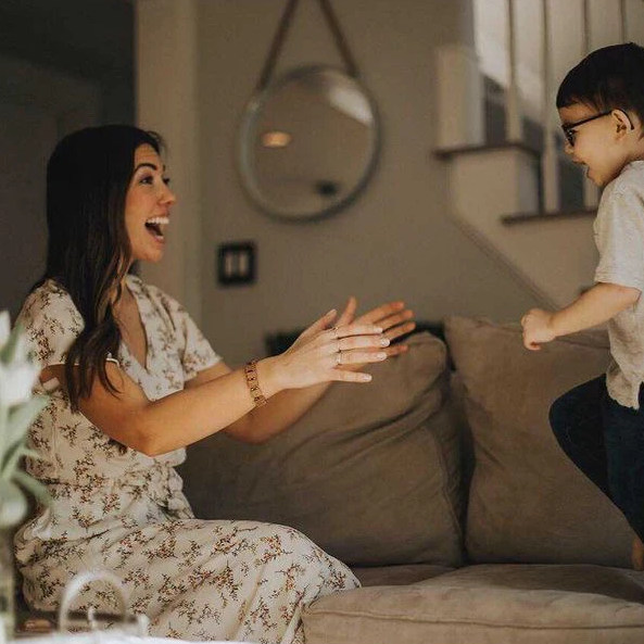 Elise is smiling excitedly as she holds open her arms for her son running towards her. She is wearing a white floral dress, with her long brown hair down.