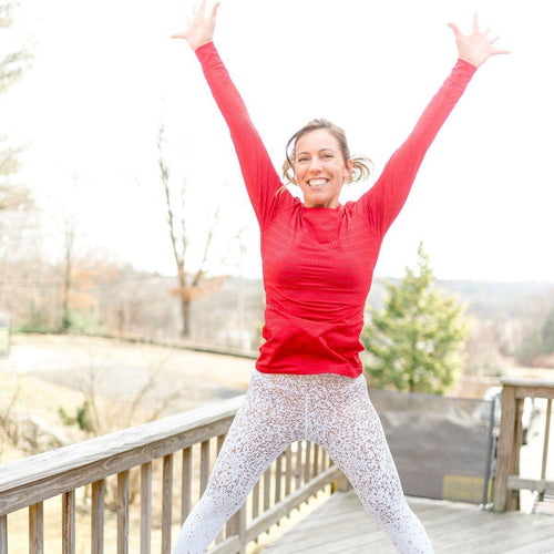 Fawn jumping in the air wearing a bright red long sleeve tee and glitter legging, looking so very happy!