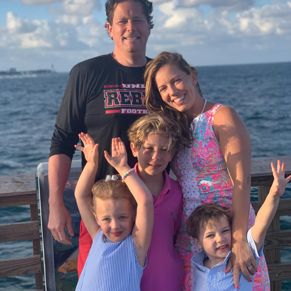 Fawn on the water with her husband, twins and step son, all dressed up on vacation